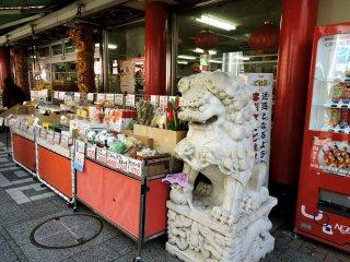 Stone lion next to a souvenir shop