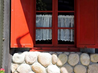Red shutters and lace curtains
