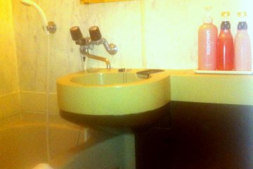 Small but practial bathroom with combined bath and shower and Shisedo Bath products at Hotel Rasso just 10 min walk from Kokusai dori