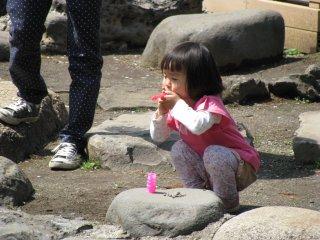 Seorang gadis kecil bermain gelembung