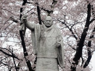 A statue of Nichiren surrounded by blossoms