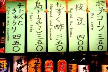 Tsumame snack menu in English and Japanese at the Barakku Bistro and Izakaya in Aharen Tokashiki-son Island Okinawa