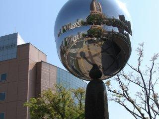 Зеркальный объект, отражающий площадь возле башни