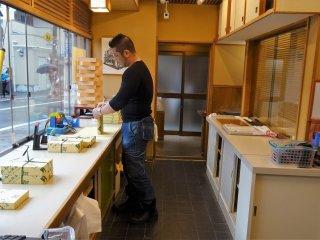 พ่อค้ากำลังแพ็คขนมคุซุโมจิ และห่อด้วยกระดาษอย่างสวยงาม