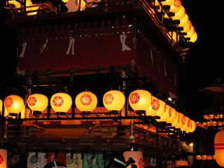 Floats are lit up with the warm light of paper lanterns