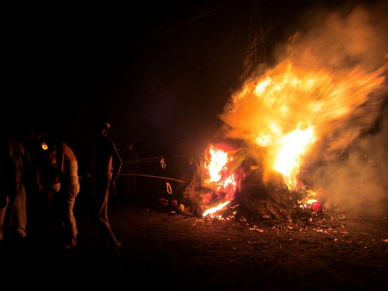 Festival-goers warm themselves by the bonfire and roast dango
