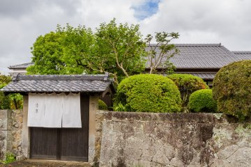 The stone wall and front gate of Katsume seclude the home and garden