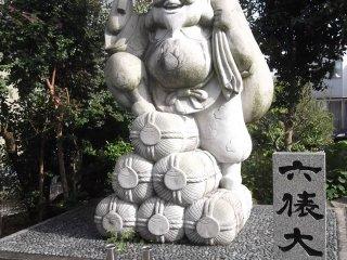 A jolly Buddhist deity with some sake barrels