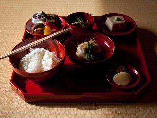 L'ensemble du repas se compose de riz, soupe, légumes, haricots et des préparations de tofu variées, le tout servi sur un plateau de laque rouge