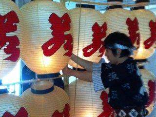 Un porteur fixe les lanternes au mât de bambou