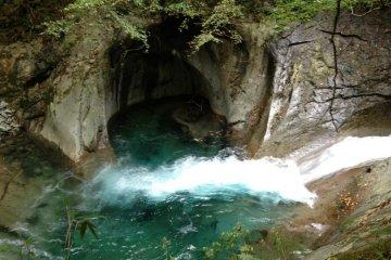 คุณจะพบกับสายน้ำสีครามที่สวยงาม เช่นสายน้ำที่ฐานของหินในถ้ำแม่น้ำขนาดเล็กนี้ ร่มเงาและสายน้ำไหลเย็นจะทำให้คุณรู้สึกเย็นสบายในช่วงฤดูร้อน