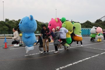 Mascots skipping together with visitors