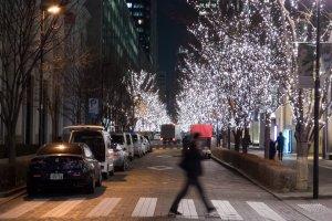Pejalan kaki yang sedang menyeberang di jalan yang terang