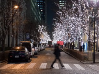 A pedestrian crosses the brightly lit street