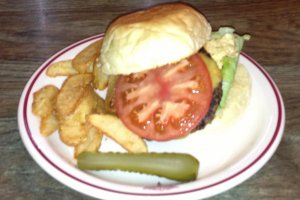 The Cheeseburger is served with seasoned french fries and a pickle slice