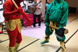 Oni demonstrate their weapons at live music event