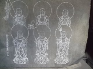 Six Buddhist figures are carved onto a large rock on an altar