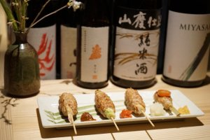 Grilled chicken meatball skewers alongside Japanese sake bottles