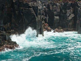 Waves crashing onto the black volcanic rocks.
