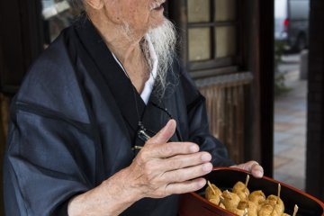 Okada stops by a shop that has been selling inari for more than 50 years