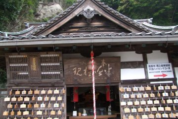 <p>A small, simple shrine with an arrow pointing towards the hiking course</p>