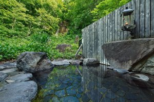 The outdoor bath of Takimi no yu with the view on the waterfall in the background