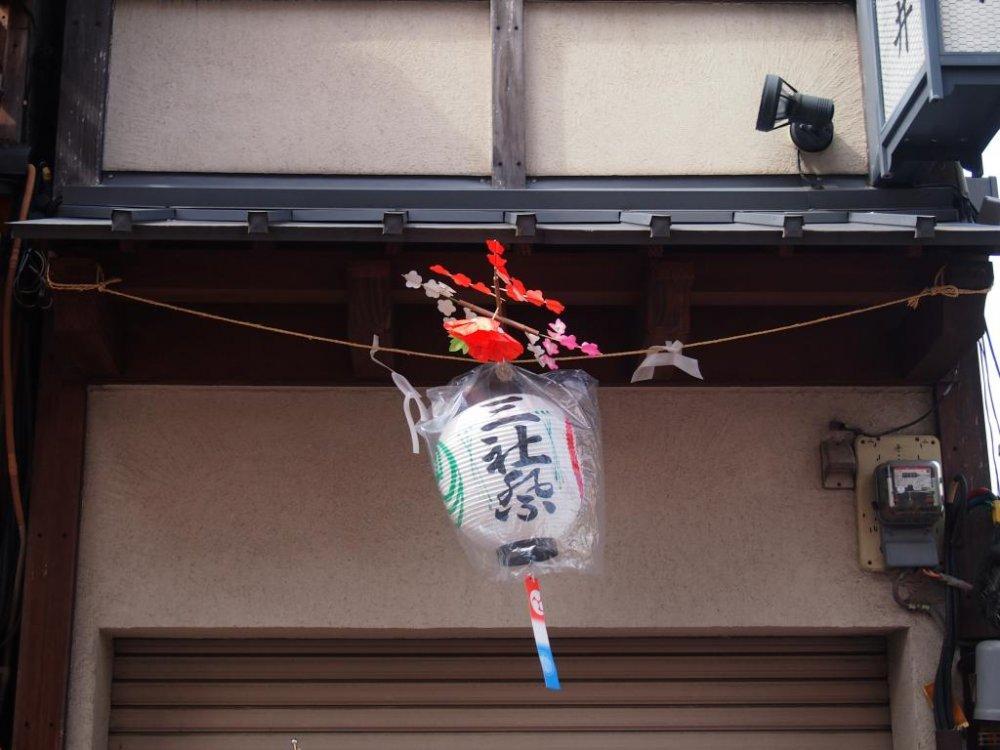Những chiếc đèn lồng ghi dòng chữ Sanja Matsuri được treo dọc mái hiên của các cửa tiệm