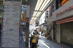 Jalan kecil yang mengarah ke bangunan kain. Jalan ini ada di sisi kanan toko aksesoris dan pakaian.