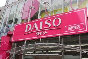 Papan nama Daiso pink raksasa memberitahukan pada orang yang lewat kalau ini adalah toko serba 100 yen