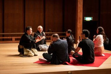 "Noh musician explains to the volunteers how to play ""fue"", the flute"