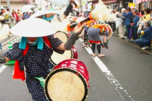 Drummers parade through the streets on their way to the rice fields