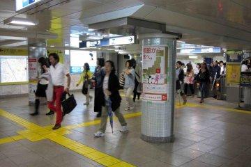 Commuters quickly walk through Ebisu Station.