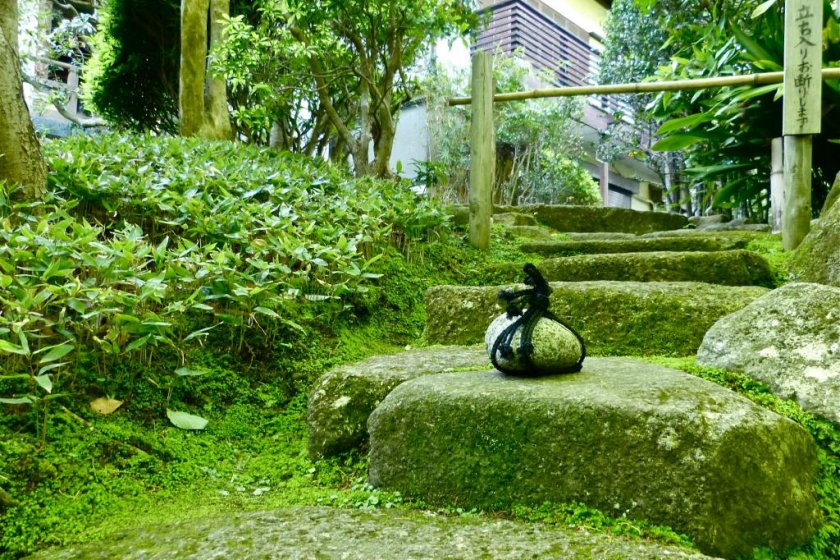 A cute round stone sitting in the middle of stone steps