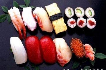 面对寿司拼盘大朵快颐