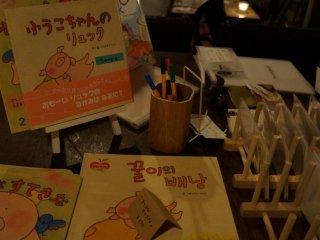 الكتب المصورة باللغة اليابانية والكورية هي أيضا على الشاشة ، جنبا إلى جنب مع جهاز كمبيوتر محمول حيث يمكن للزوار تبادل التعليقات حول المقهى والعمل الفني .