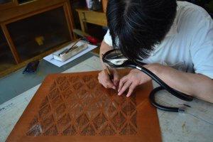 Pak Ono, manajer toko, menunjukkan proses pemotongan stensil yang harus sangat hati-hati