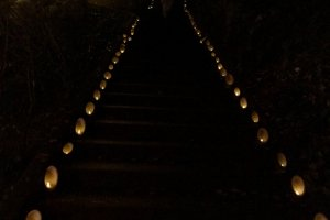 Jalan curam menuju tempat festival dan panggung diterangi dengan lilin-lilin kecil dengan sempurna