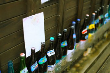 Sake bottles line the streets of a Daimyo izakaya