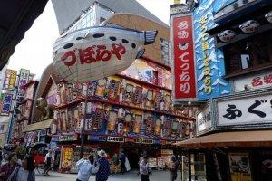 Por trás do balão gigante do fugu vê-se a fachada do velho teatro
