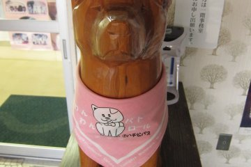 <p>Miniature wooden Akita dog on display</p>
