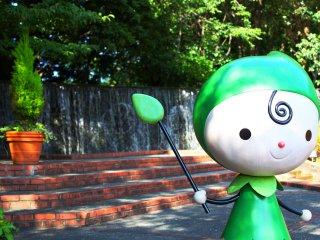 A mascote do parque a acenar em frente à fonte