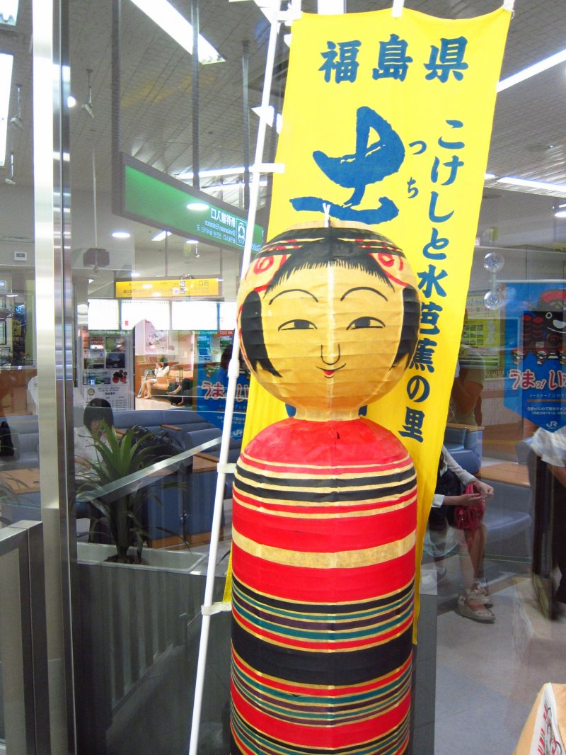 Kokeshi Doll standing guard over the JR gates