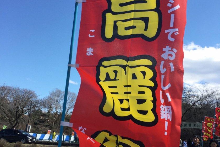 Biểu ngữ quảng cáo Koma nabe, món ăn đã giành giải Grand Prix tại cuộc thi B-Gourmet. Koma Nabe bao gồm kim chi, rau tươi và nhân sâm Hàn Quốc.
