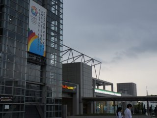 ป้ายทางซ้ายมือโฆษณาโอลิมปิคและพาราลิมปิค 2020 ซึ่งโตเกียวได้สมัครลงชื่อไว้ หากได้รับเลือกโตเกียว บิค ไซท์ก็จะได้เป็นสถานที่จัดการแข่งขันจำพวกมวยปล้ำ ยกน้ำหนัก เทควนโด และการแข่งขันฟันดาบ