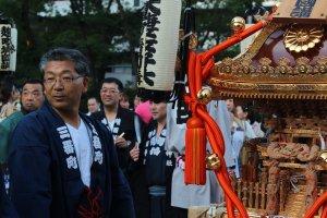 Đứng cạnh một trong nhiều mikoshi (kiệu rước)
