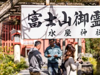 A sign points the way to a water collection station where visitors can bottle the shrine's sacred waters to take home