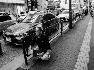 A Japanese middle-aged man squats down by the sidewalk and take a smoke break.