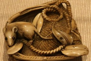 A highly detailed rat in a basket netsuke