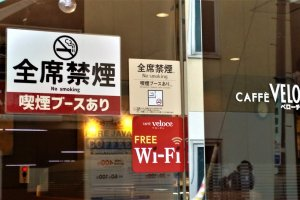 """The sign of the cafe Veloce in Shibuya says, """"No smoking but a smoking booth is available"""""""