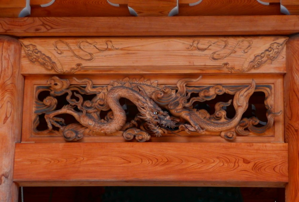 The beautifully detailed carvings along the roof protecting the bell